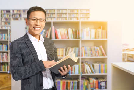 Photo for Handsome Asian man with book in modern library - Royalty Free Image