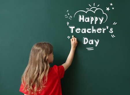 Photo pour Cute little schoolgirl writing text HAPPY TEACHER'S DAY on blackboard in classroom - image libre de droit