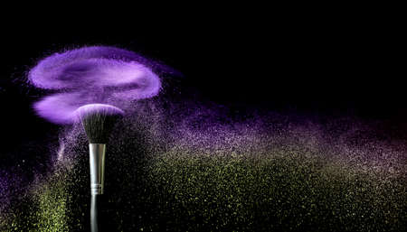 Photo for Makeup brush and burst of cosmetics on dark background - Royalty Free Image