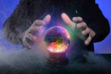 Photo pour Fortune teller with crystal ball on color background, closeup - image libre de droit