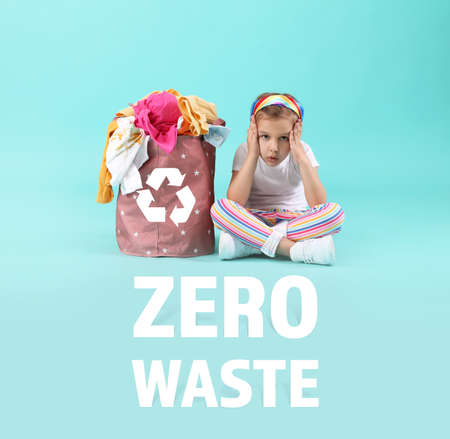 Photo for Concerned little girl with clothes in basket on color background. Zero waste concept - Royalty Free Image