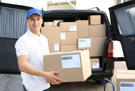 Photo for Handsome delivery man near car with parcels outdoors - Royalty Free Image