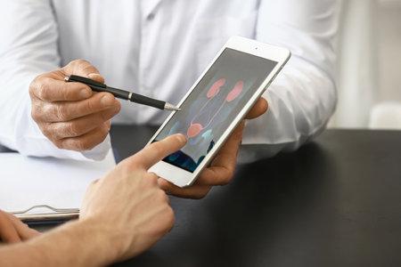 Photo pour Urologist with table computer explaining patient his diagnosis, closeup - image libre de droit