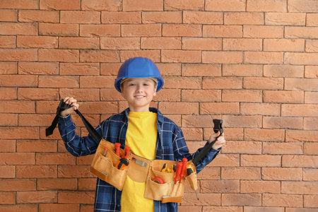 Photo pour Cute little mechanic with tools near brick wall - image libre de droit