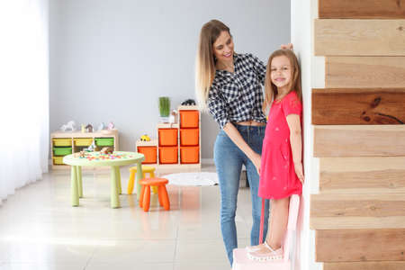 Photo pour Young mother measuring height of her little daughter at home - image libre de droit