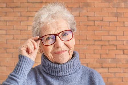 Photo pour Portrait of senior woman on brick background - image libre de droit