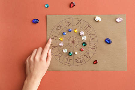 Photo pour Astrological horoscope with birthstones and female hand on color background - image libre de droit