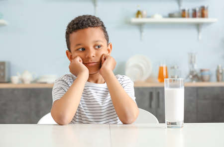Photo pour Cute African-American boy with glass of milk at table - image libre de droit