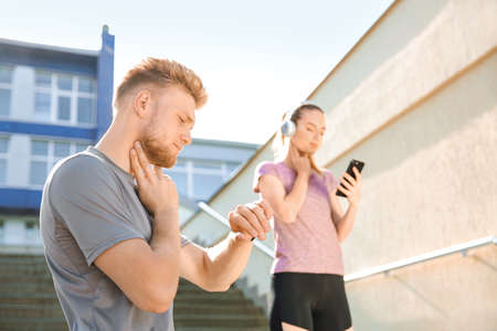 Photo for Sporty young people checking pulse outdoors - Royalty Free Image