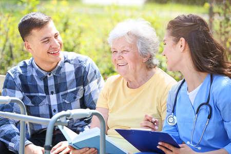 Photo pour Caregiver and grandson with senior woman in park - image libre de droit