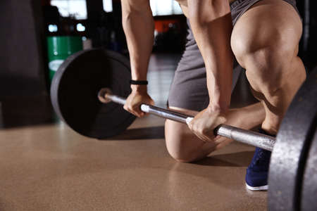 Photo pour Sporty young man training with barbell in gym - image libre de droit