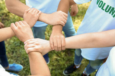 Photo pour Team of volunteers holding hands together outdoors - image libre de droit
