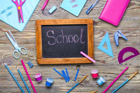 Photo for Set of school supplies with chalkboard on wooden background - Royalty Free Image