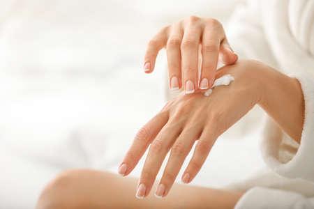 Photo pour Young woman applying natural cream onto skin at home - image libre de droit