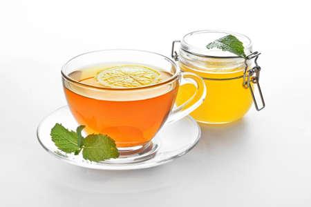 Photo pour Glass cup of tasty tea with honey, mint and lemon on white background - image libre de droit