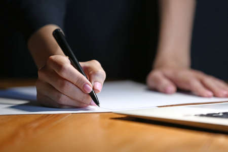 Photo pour Woman writing something on sheet of paper at workplace in evening, closeup - image libre de droit