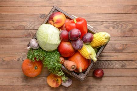 Foto für Box with many healthy vegetables and fruits on wooden background - Lizenzfreies Bild