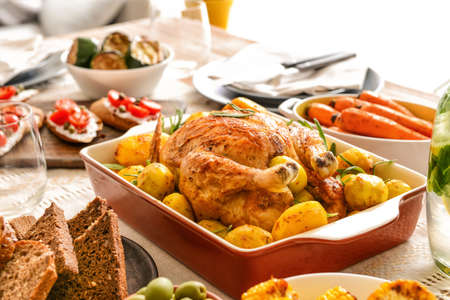 Photo for Baking dish with tasty chicken and potato on served table - Royalty Free Image