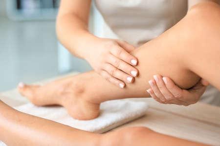 Foto de Beautiful young woman receiving foot massage in spa salon - Imagen libre de derechos