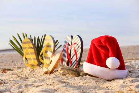 Photo pour Santa Claus hat with flip-flops and wooden airplane on sea coast. Christmas vacation - image libre de droit