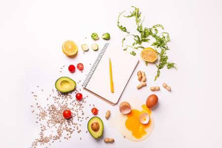 Photo for Notebook with healthy products on white background. Diet concept - Royalty Free Image