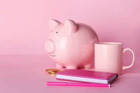 Photo pour Piggy bank with stationery and cup on color background - image libre de droit
