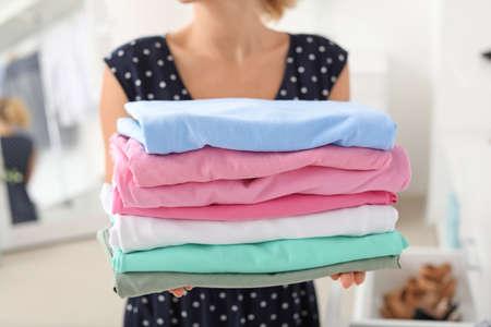 Photo pour Woman with stack of clean clothes at home, closeup - image libre de droit