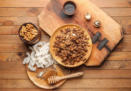 Photo for Tasty granola with coconut, honey and nuts on wooden table - Royalty Free Image