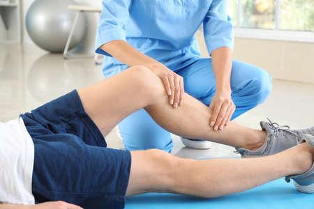 Photo pour Physiotherapist working with male patient in rehabilitation center - image libre de droit