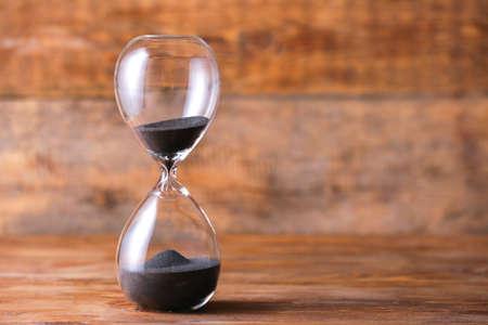 Photo pour Crystal hourglass on wooden background - image libre de droit