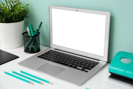 Foto de Comfortable workplace with modern laptop near color wall - Imagen libre de derechos