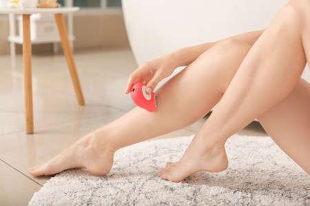 Photo pour Beautiful young woman epilating of legs in bathroom - image libre de droit