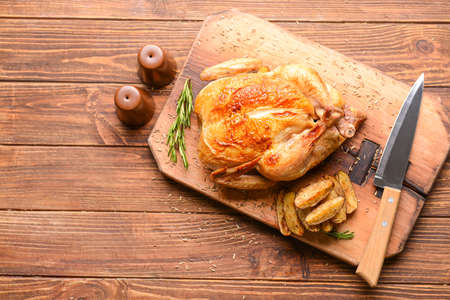 Photo pour Board with baked chicken and potato on wooden table - image libre de droit