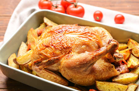 Photo pour Dish with baked chicken and potato on wooden table - image libre de droit