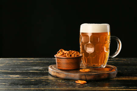 Photo pour Mug of fresh beer and snack on wooden table - image libre de droit