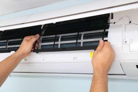 Photo pour Male technician repairing air conditioner indoors, closeup - image libre de droit
