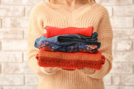 Photo pour Woman with stack of warm clothes on brick background - image libre de droit