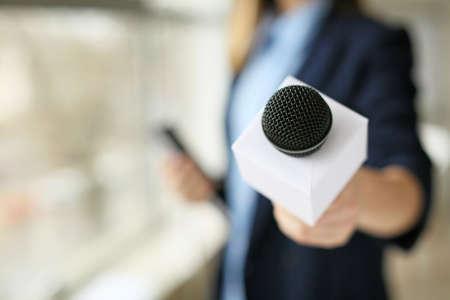 Photo pour Female journalist with microphone in office, closeup - image libre de droit