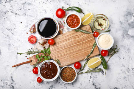 Photo pour Bowls with tasty sauces, ingredients and wooden board on white background - image libre de droit