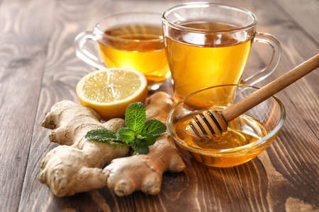 Foto für Cups of healthy drink with lemon, ginger and honey on wooden table - Lizenzfreies Bild