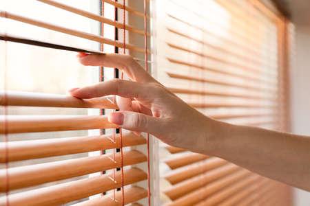 Photo pour Woman opening blinds on window - image libre de droit