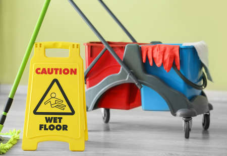 Photo pour Caution sign with janitor's trolley indoors - image libre de droit