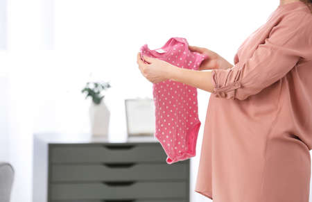 Photo pour Pregnant woman with baby clothes at home, closeup - image libre de droit