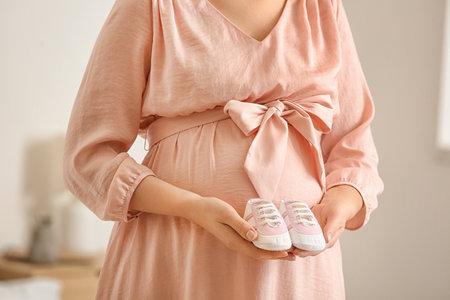Photo pour Pregnant woman with baby shoes in bedroom, closeup - image libre de droit