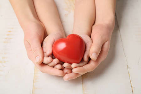 Photo pour Hands of woman and child with red heart on wooden background. Cardiology concept - image libre de droit
