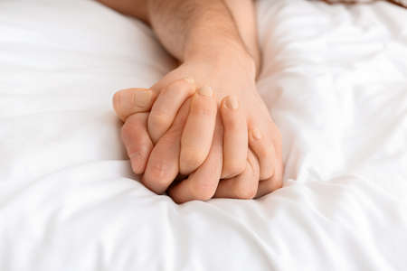 Photo pour Hands of young couple sleeping in bed - image libre de droit
