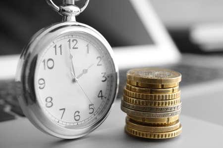 Photo pour Coins and clock on laptop, closeup. Time management concept - image libre de droit