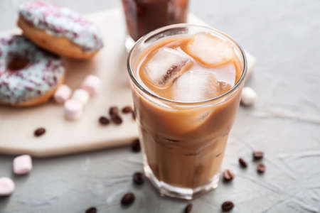 Photo for Glass of tasty iced coffee on gray background - Royalty Free Image