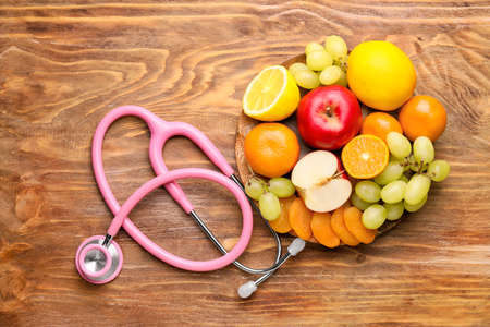 Photo pour Plate with healthy products and stethoscope on wooden table - image libre de droit