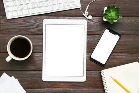 Photo for Mobile phone, PC keyboard, tablet computer, cup of coffee and stationery on wooden background - Royalty Free Image